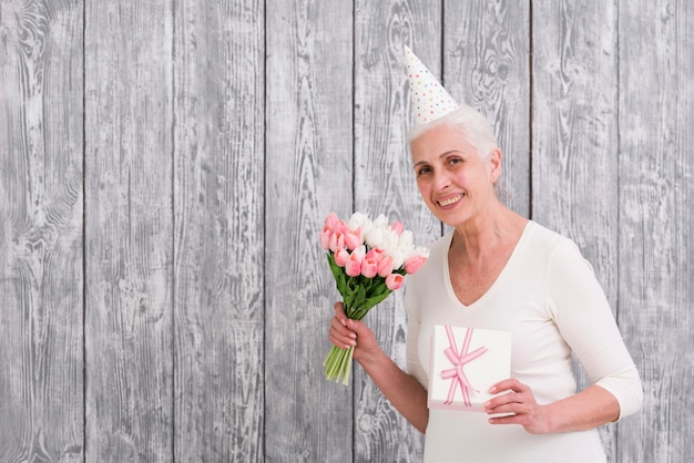 Smiling senior birthday woman holding tulip flower bouquet and gift box in front of wooden backdrop