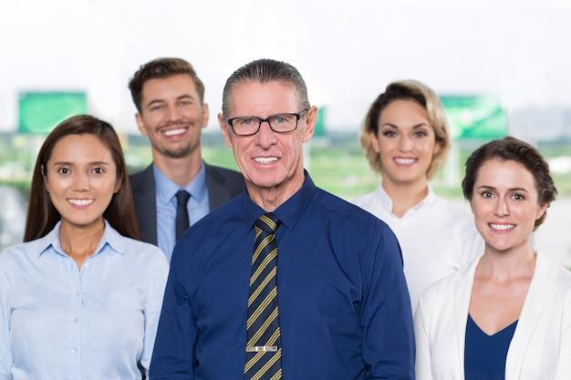 Улыбаясь старший бизнес-лидер стоя с командой