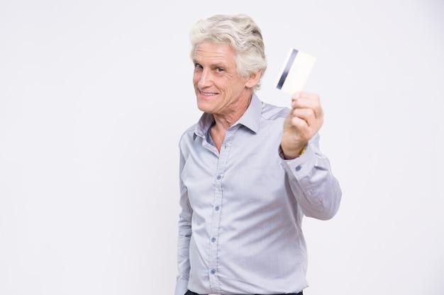 Smiling senior businessman holding credit card