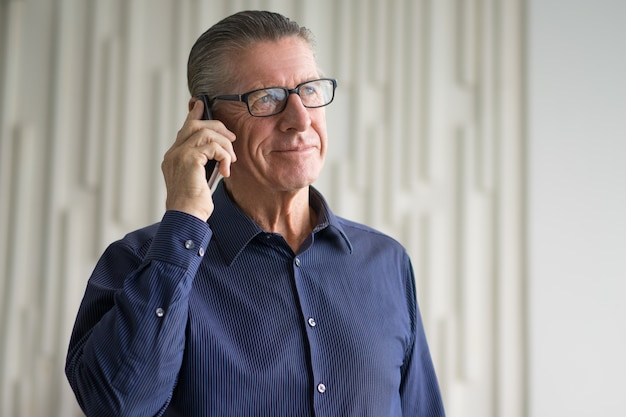 Smiling senior businessman talking on smartphone