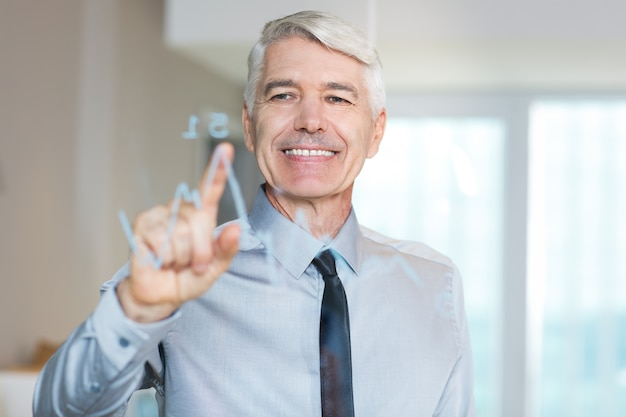 Smiling senior businessman touching glass screen