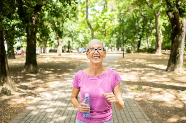 공원에서 조깅 하는 수석 백인 여자 웃 고.