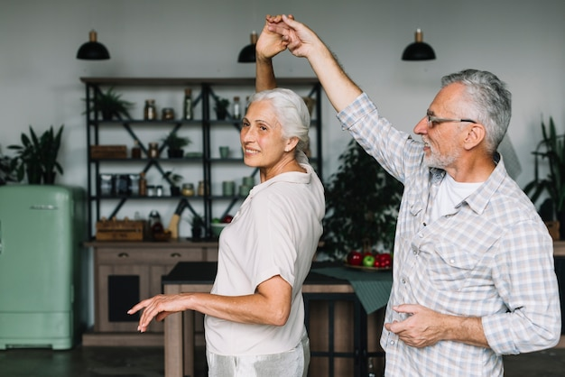 Smiling senior couple dancing together in the kitchen