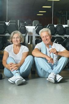 체육관에서 운동한 후 웃고 있는 노부부 식수