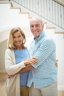 Улыбающиеся старшие пары, обнимая друг друга в гостиной