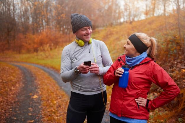 ジョギングから休憩している笑顔の年配のカップル