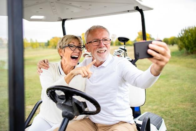 Улыбающаяся старшая пара веселится на поле для гольфа и делает селфи в машине для гольфа перед тренировкой