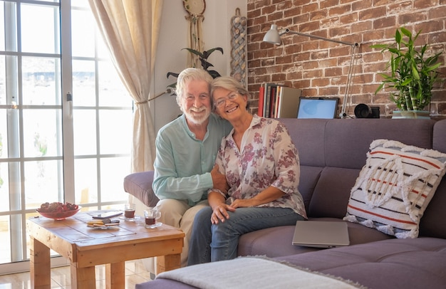 Smiling senior couple at home sitting on sofa looking at camera. brick wall on background
