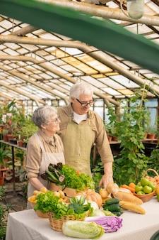 Улыбающаяся старшая пара в фартуках, стоящая за столом с различными продуктами и продающая овощи из своего сада