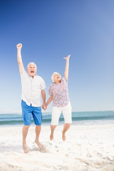 Smiling senior couple jumping