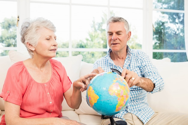 Smiling senior couple looking at globe on the sofa