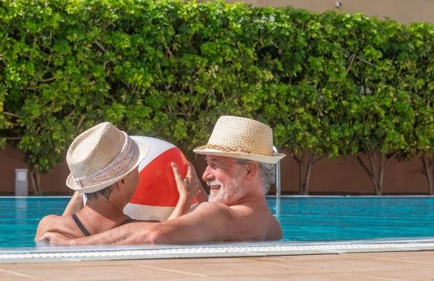 Улыбаясь старшая пара играет в бассейне с надувным мячом. счастливые пенсионеры наслаждаются летними каникулами под солнцем