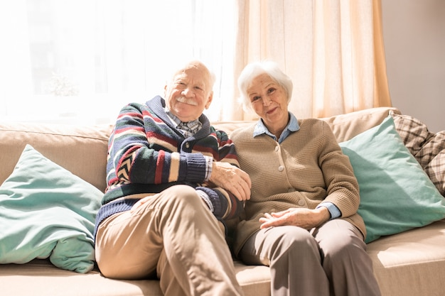 Smiling senior couple posing on sofa in sunlight