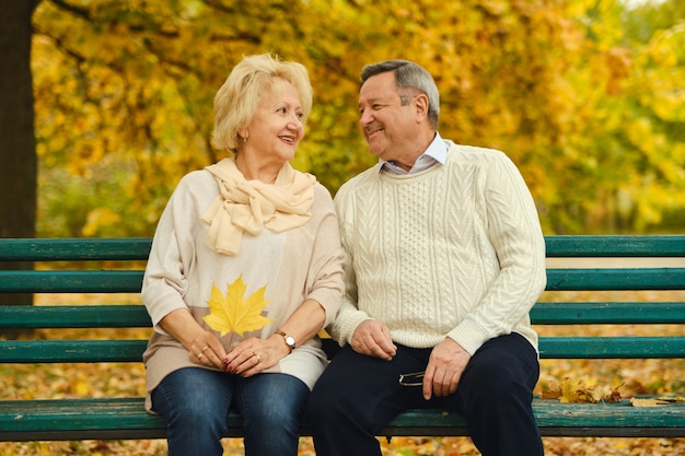 Smiling senior couple sitting on the bench in the park together enjoying retirement