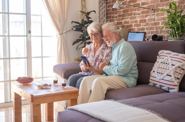 Улыбаясь старшая пара, сидя на диване у себя дома, используя телефон, наслаждаясь технологиями и выходом на пенсию