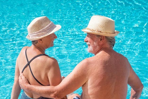 수영장 가장자리에 앉아 서로의 눈을 바라보며 웃고 있는 노부부. 두 명의 행복한 은퇴자는 태양 아래서 여름 휴가를 즐긴다