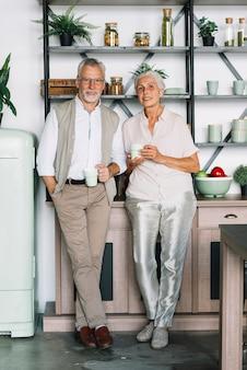 コーヒーの棚の前に立っている笑顔のシニアカップル