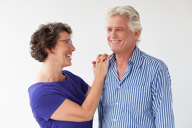 Smiling senior couple talking and embracing