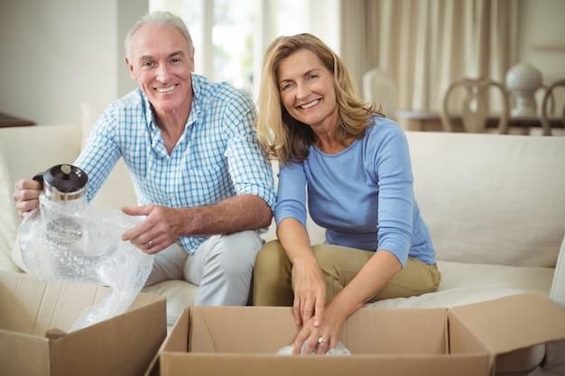 リビングルームで段ボール箱を開梱する笑顔の年配のカップル