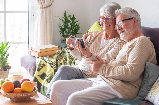 소파에서 집에서 휴식을 취하는 전화를 사용하여 웃는 노부부