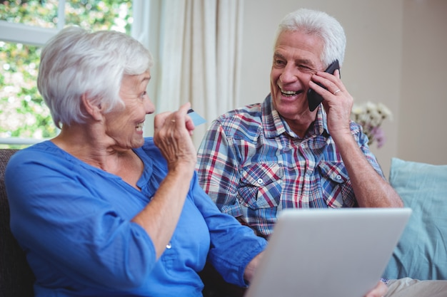 Smiling senior couple using technology