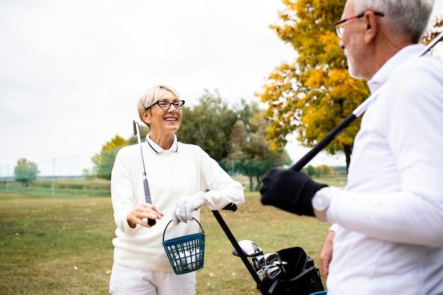 Улыбаясь старшие пары с оборудованием для гольфа, говоря перед тренировкой.