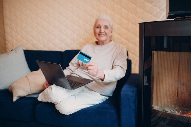 Smiling senior ederly woman using credit bank card and laptop on sofa near fireplace. online shopping concept.