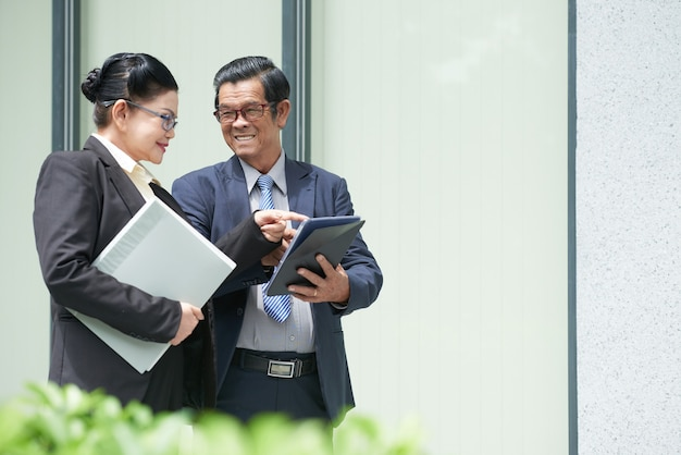Smiling senior entrepreneur showing contract or article on tablet computer to colleague when they are standing on the street