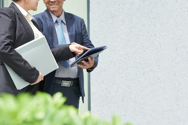 Smiling senior entrepreneurs standing outdoors and discussing data on digital tablet