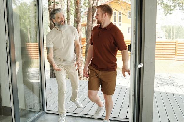 裏庭を散歩した後、別荘に来て話している先輩父と大人の息子の笑顔