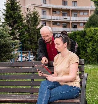 デジタルタブレットを使用して公園で休んでいる娘と一緒に先輩の父を笑顔