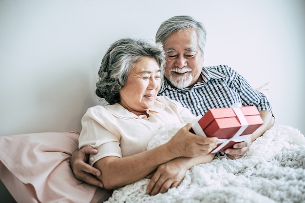 Smiling senior husband making surprise giving gift box to his wife in bedroom