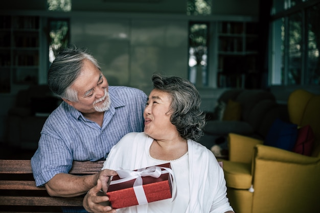Smiling senior husband making surprise giving gift box to his wife