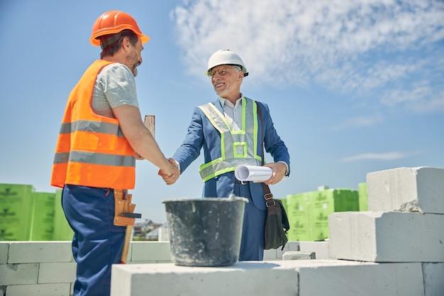 Улыбающийся старший подрядчик-мужчина в очках и каменщик в шлеме приветствуют друг друга