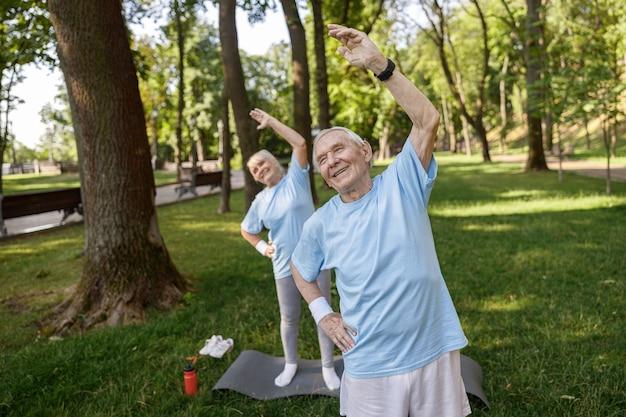 Улыбающиеся старшие мужчина и женщина делают боковые повороты на пышной лужайке в городском парке