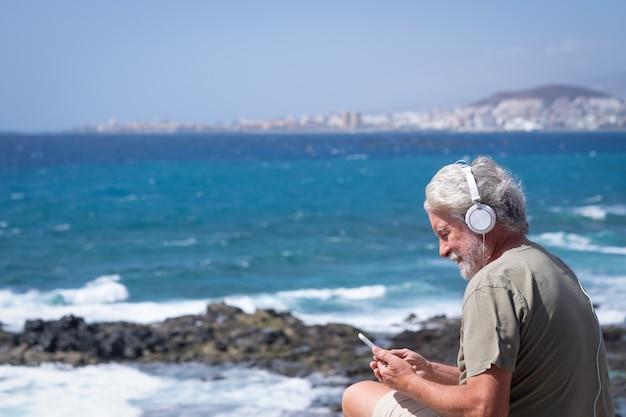 바람이 부는 날 바다에서 전화를 사용하여 웃고 있는 노인, 수염, 흰 머리. 자연 속에서 휴가와 아름다움을 즐기는 노인들