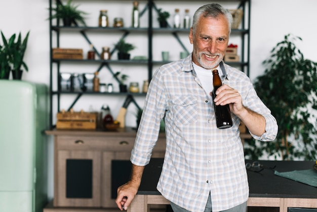 Smiling senior man drinking beer from bottle at home