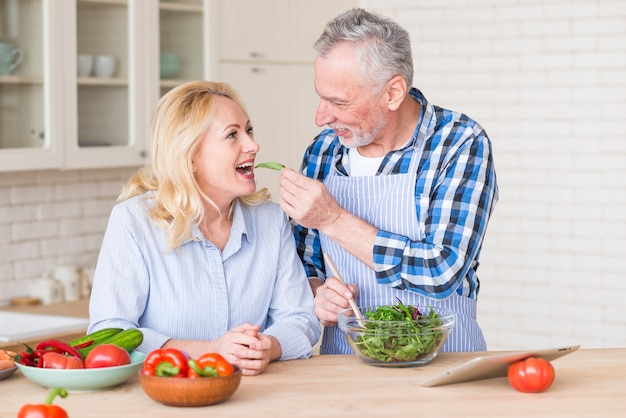 Smiling senior man feeding fresh green salad to her wife in the kitchen