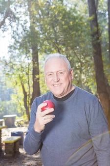 Smiling senior man holding an apple after exercise
