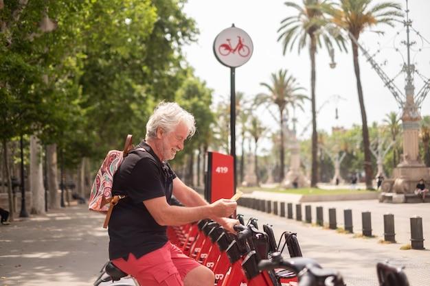 公園で電動自転車を借りてクレジットカードを持っている笑顔の年配の男性。街の暮らし