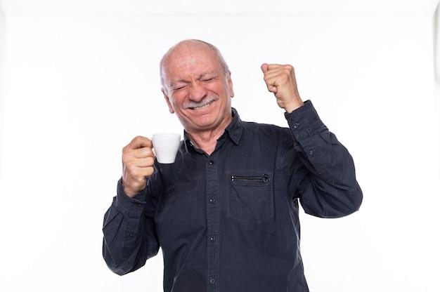 一杯のコーヒーを持って笑顔の年配の男性