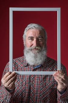 Smiling senior man holding white border frame against colored background