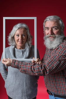 Smiling senior man holding white frame border in front of his wife's face against red backdrop
