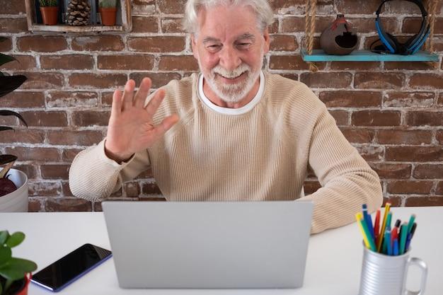 Улыбающийся старший мужчина в видеозвонке с портативным компьютером у себя дома. кирпичная стена на фоне