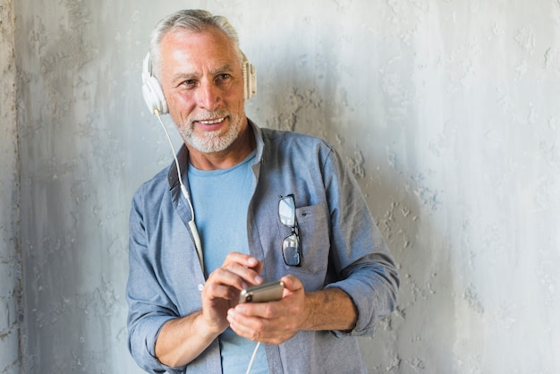 Smiling senior man listening music on headphone through mobile