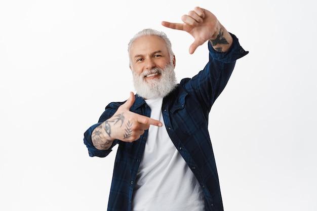 笑顔の年配の男性は、白い壁の上に立って、写真を撮り、笑顔で、笑いながらあなたを見ながらスナップを作り、ハンドフレームのカメラジェスチャーを行います