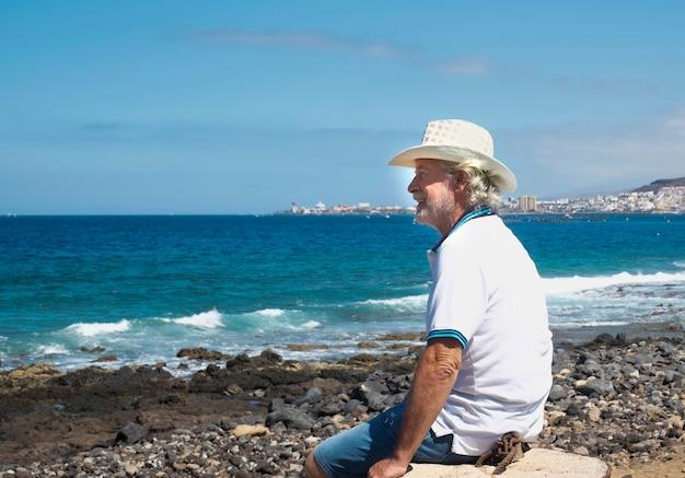 水上の地平線を見ている小石のビーチで笑顔の年配の男性。彼の後ろの青い空と海。健康的な生活様式。幸せな退職の概念