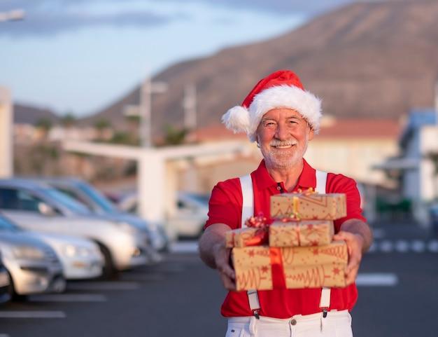 Улыбающийся старший мужчина делает покупки на рождество в шляпе санта-клауса и подтяжках, держа подарочные коробки