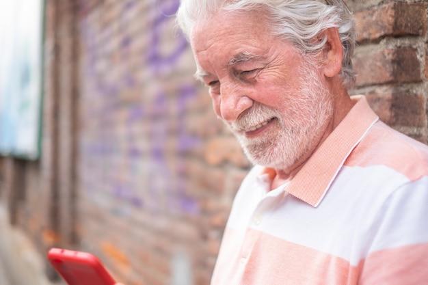 휴대 전화, 도시 생활을 사용하여 벽돌 벽에 야외에 서있는 웃는 노인
