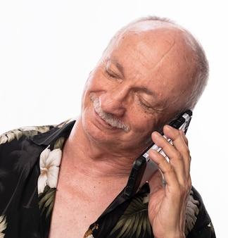 白い背景の上の電話で話している年配の男性の笑顔
